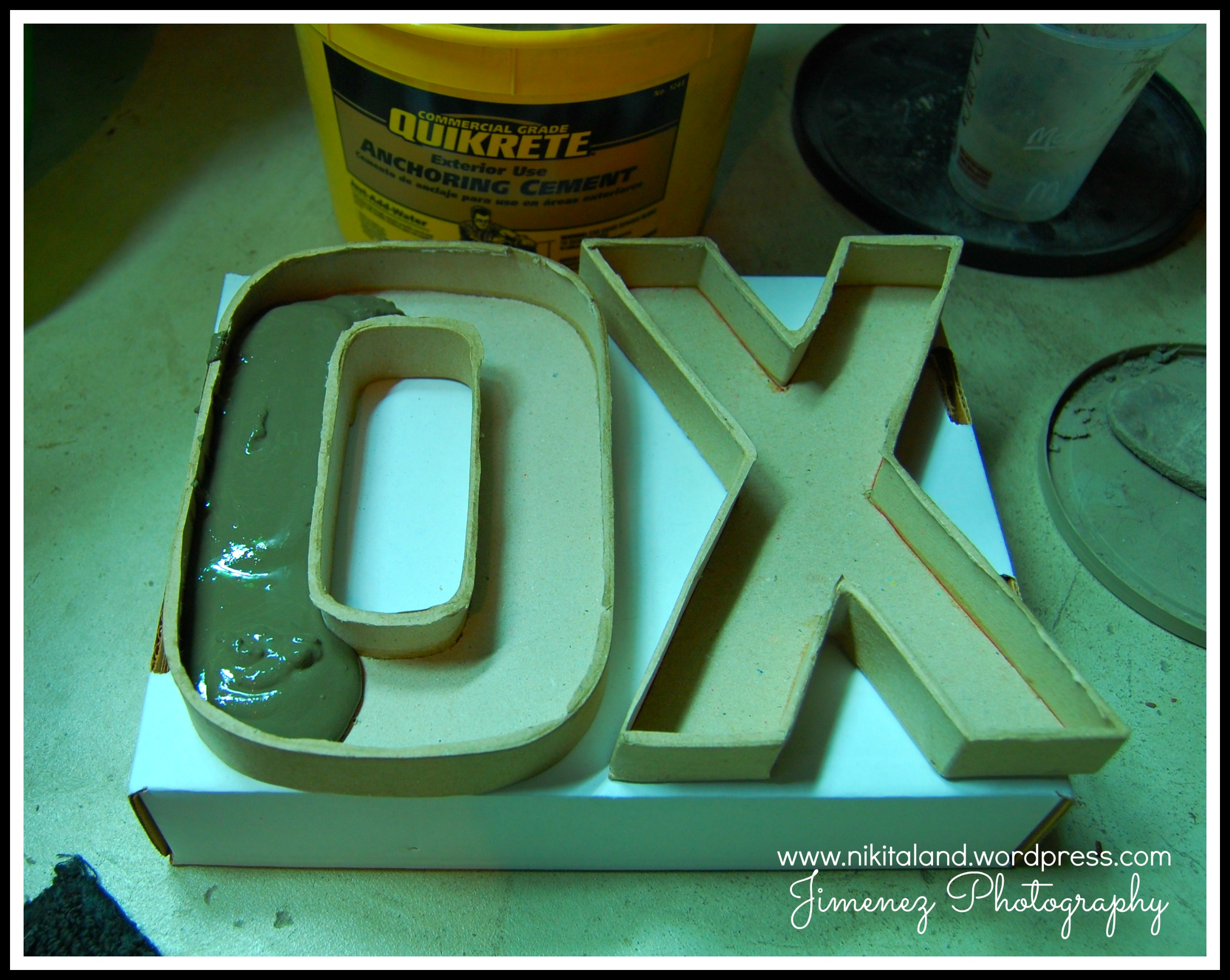 filling up cardboard letter molds with cement