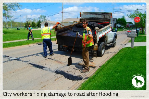 CITY WORKERS FIXING ROAD AFTER FLOODING